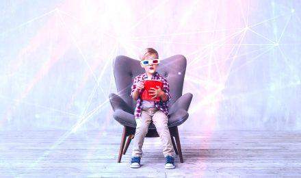 Pojke i fåtölj med 3d-glasögon och popcornhink